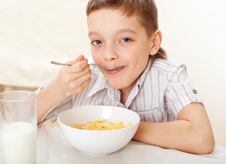 Child eat breakfast. Boy eating cereals with milk photo