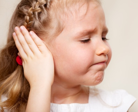 human ear: Child has a sore ear. Little girl suffering from otitis