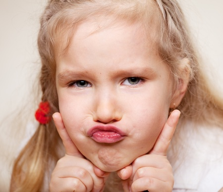 grimacing: Grimacing child. Hamming little girl. Stock Photo