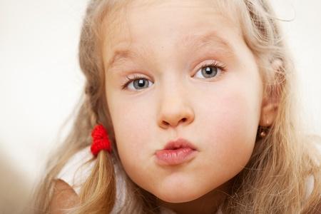grimacing: Grimacing child. Surprised little girl.