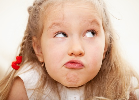 surprised child: Grimacing child. Nescience little girl. I do not know Stock Photo