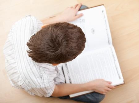 Niño leyendo un libro en el piso en su casa Foto de archivo - 13084971