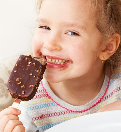messy kids: Child eating ice cream. Little girl at home