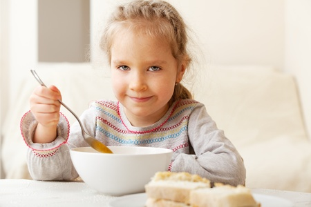 Child eating soup at home. Little girl have a dinner photo