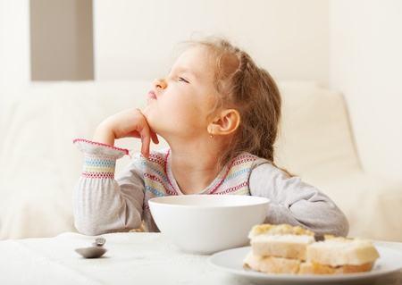 angry blonde: Child looks with disgust for food.  Stock Photo