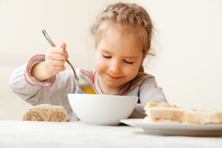 Child eating soup at home. Little girl have a dinner