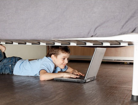 dependence: Child playing laptop under the bed. Computer Addiction Stock Photo