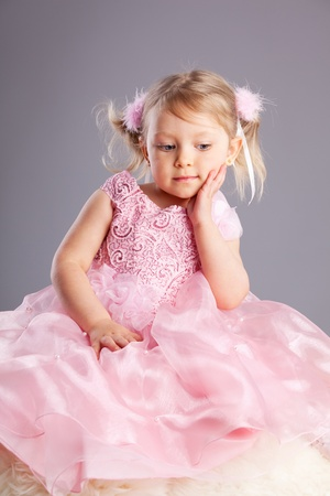 Beautiful little girl on a gray background photo