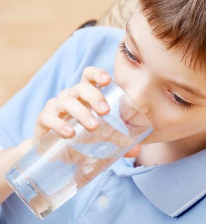 sediento: Ni�o de agua potable. Boy agua potable de un vaso Foto de archivo