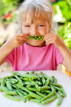 green pea: Child eating pea pod outdoors