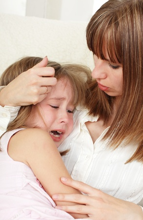 consoling: Mother calms the crying daughter