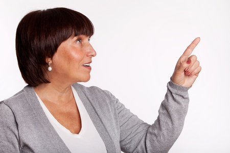 Mid woman showing a finger in the direction. Isolated on gray Stock Photo - 13086346