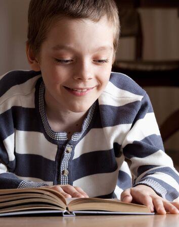 Child reeding book lying on the floor Stock Photo