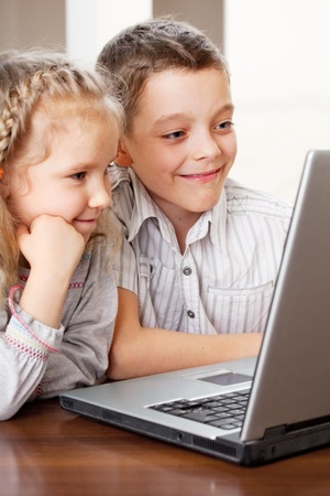 Children with laptop indoors. Happy kids playing computer at home. Stock Photo - 13200910