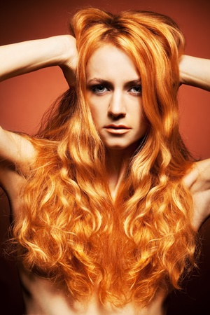 Fashion portrait of redhead woman with long hair on brown background photo
