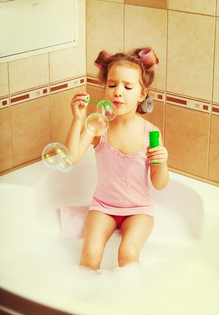 curler: Glamour girl blow bubbles in the bathtub. Child in bathroom