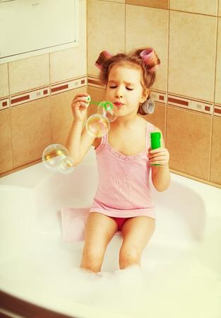 little girl bath: Glamour girl blow bubbles in the bathtub. Child in bathroom