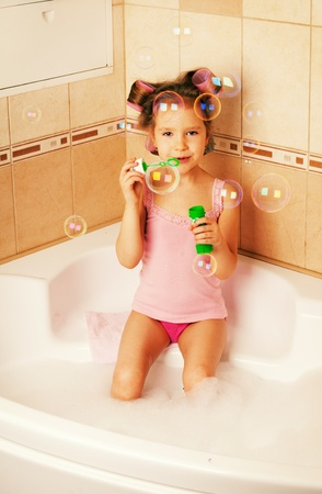 bathtub: Glamour girl blow bubbles in the bathtub. Child in bathroom