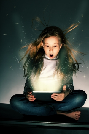 Surprised girl looking at a magic tablet. Child with tablet computer photo