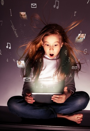 Surprised girl with tablets in hand. Flow of information, letters, photos departing from the tablet photo