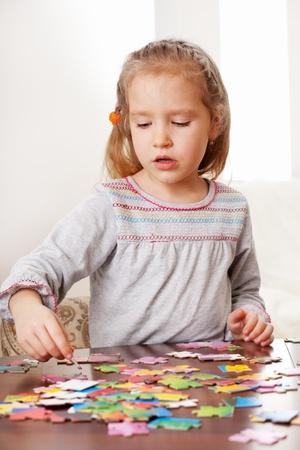 niños pensando: Niño jugando rompecabezas. Juego de niña en el hogar Foto de archivo