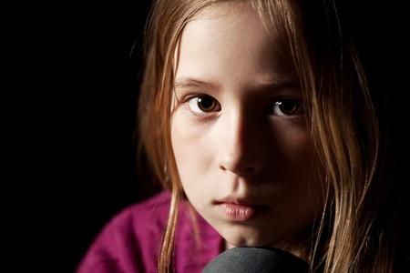child sad: Sad child on black background. Portrait depression girl