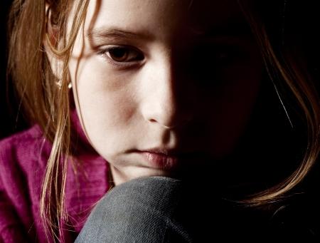 maltrato infantil: Niño triste sobre fondo negro. Retrato de niña la depresión