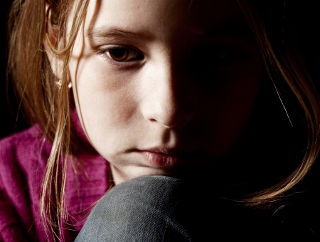 Sad child on black background. Portrait depression girl photo