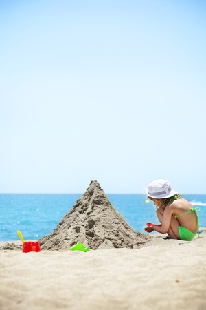 sand castle: Girl building sand castle on the beach. Child playing on the beach Stock Photo