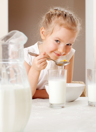 melk glas: Kind ontbijten. Meisje eet cornflakes met melk Stockfoto