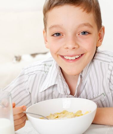 Child eating frosted flakes at breakfast photo