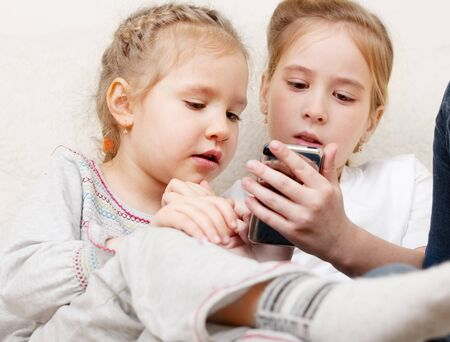 Children with mobile phone. Girls playing on smart phone photo