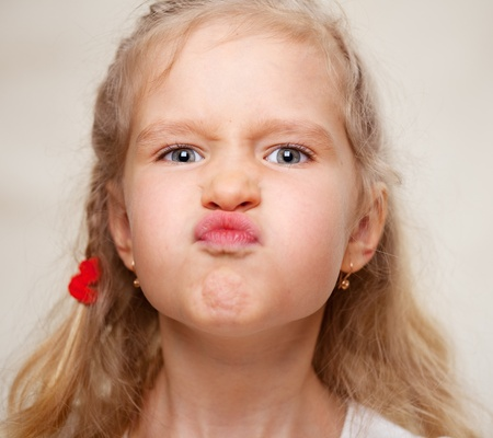 grimacing: Grimacing child. Hamming little girl. Stock Photo