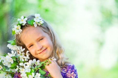 Child in spring park. Girl with blossoming apple tree photo