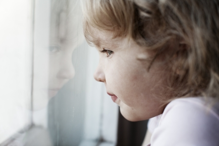 Sad little girl looking at window photo