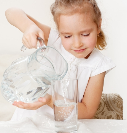 Child with glass pitcher water. Little girl drinking water at home photo