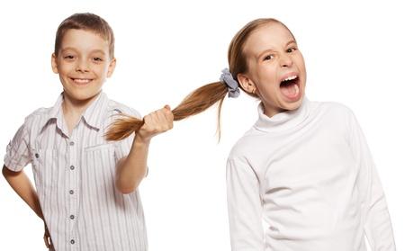 anger: Boy tira de los pelos de la chica aisladas sobre fondo blanco. Los conflictos de los ni�os
