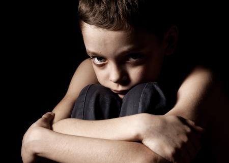 niños tristes: Muchacho triste sobre fondo negro. Retrato niño de la depresión