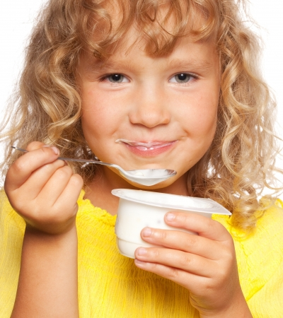 Little child eating yogurt photo