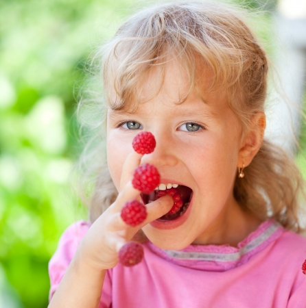 child finger: Happy little child with raspberry outdoors