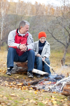 Grandfather and grandson around a campfire in the woods photo