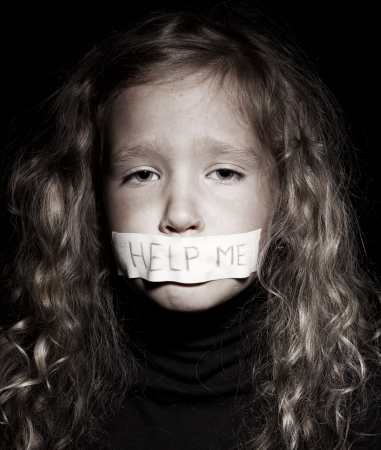 abuse: Little child with taped mouth, begging for help. Sad, abuse girl. Violence, despair.