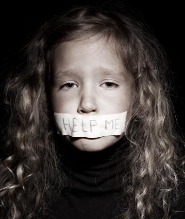 maltrato: Peque�o ni�o con la boca pegada, pidiendo ayuda. Triste, el abuso de ni�a. La violencia, la desesperaci�n.