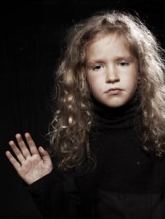 think through: Sad little girl near window. Depression child