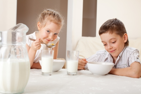 Children eat breakfast. Family eating cereals with milk photo
