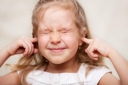 shut: Child closed her ears. Portrait closeup.