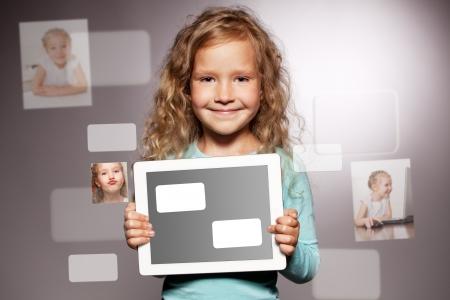 Niño feliz con equipo Tablet PC. Kid mostrando pantalla de la tablet Foto de archivo