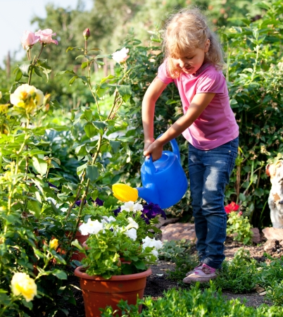 Child watered from watering the flowers in the garden photo
