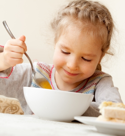 kid eat: Child eating soup at home. Little girl have a dinner