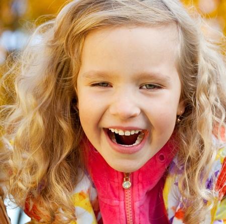 Little happy girl in autumn park photo